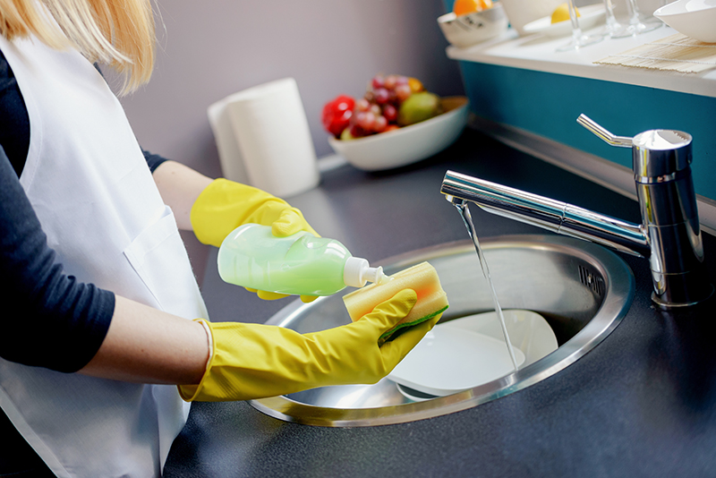 Woman cleaning counter with rubber gloves chemicals
